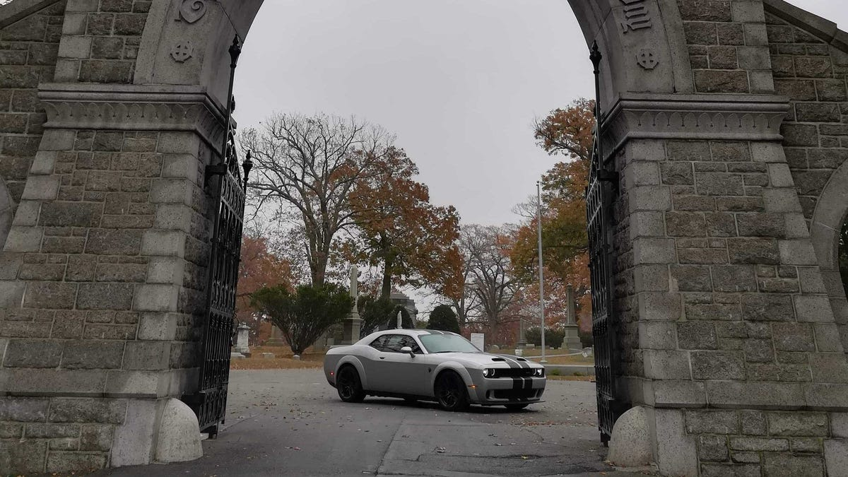 "Happy Halloween. Our own Erin Marquis is currently on a ""spooky"" road trip in a fairly scary car, the Dodge Challenger Hellcat Redeye. Here she is at Lizzie Borden's gravesite at Fall River, Mass."