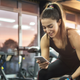 woman looking at phone in the gym