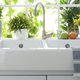 Photo of a white porcelain sink with two basins in front of a window filled with plants. There's a blue and white striped towel hanging over the right side of the sink.