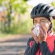 Cyclist blowing her nose