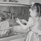 A girl washing dishes at the sink in a vintage black and white photo