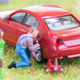A toy man changes a tire on a model car