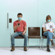 two people in masks sitting in a waiting room