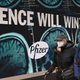 """people in masks in front of a big Pfizer ad that says """"SCIENCE WILL WIN"""""""
