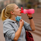 woman pulls down mask to have a drink of water after jogging