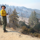Elizabeth Wright with the Forest Service monitors a firefighting helicopter making water drops during the Bobcat Fire in the Angeles National Forest on Sept. 16, 2020 near Pasadena, California.
