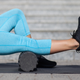 Person in blue leggings foam rolling her calf