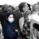 Woman with a mask is surrounded by unmasked people