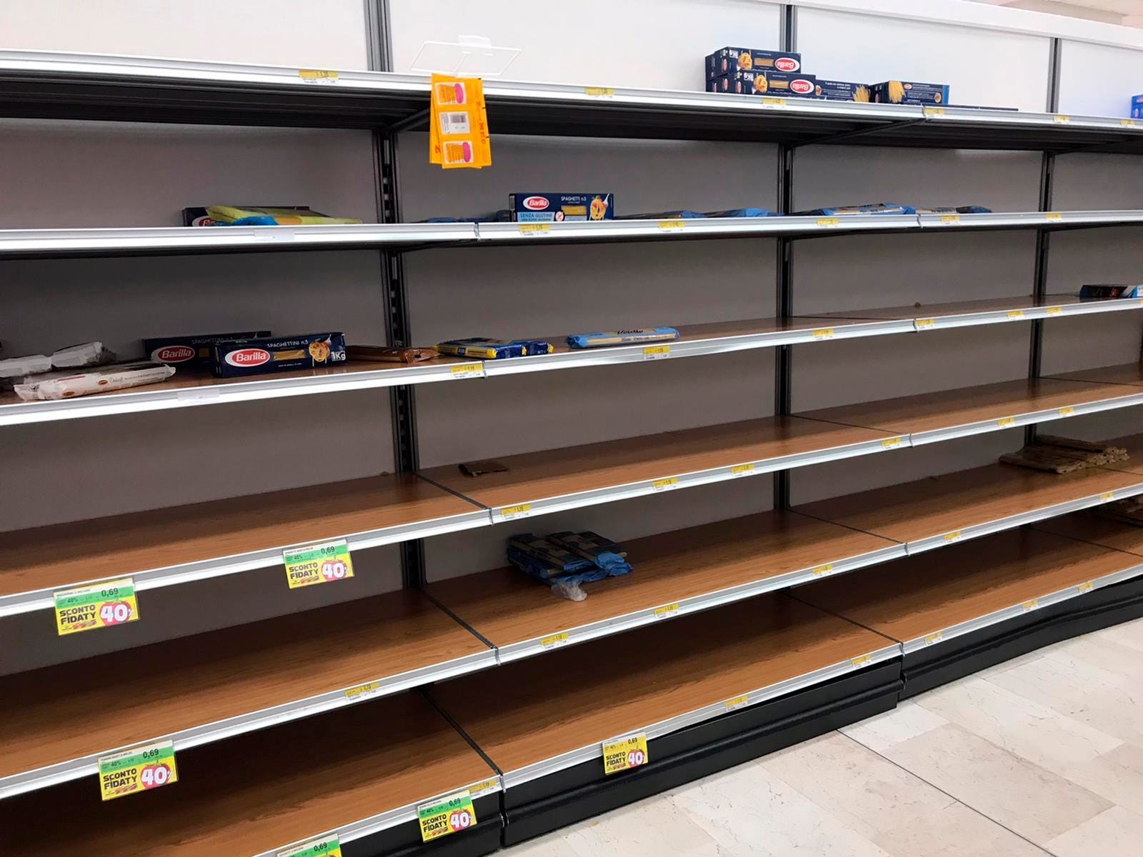 Empty shelves are seen in a supermarket in Rozzano, near Milan, Sunday, Feb. 23, 2020, as fears rapidly spread in Northern Italy with a sudden surge of COVID-19 cases.