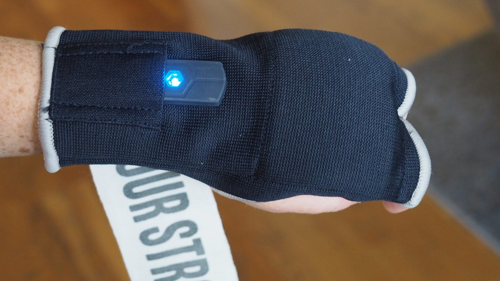 The tracker with the blue light slides into the blue hand wrap.