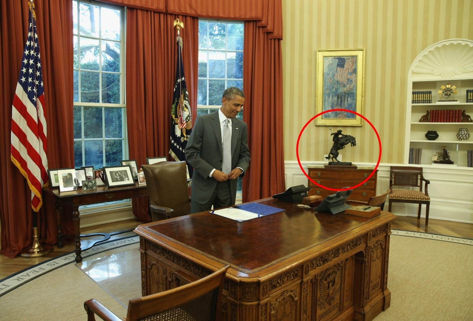 President Barack Obama stands at his desk on August 4, 2014 in Washington, DC. with the Bronco Buster sculpture highlighted in the background