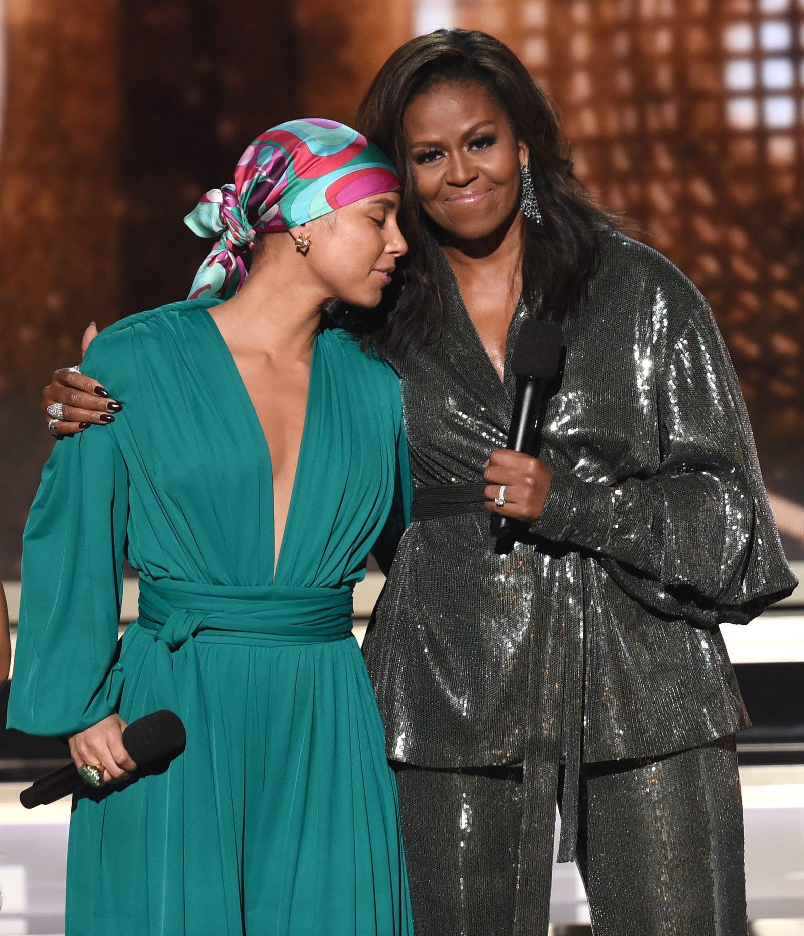 Alicia Keys (l) hugs Michelle Obama, who is wearing custom Sachin and Babi.