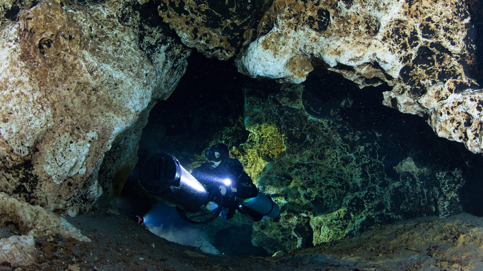 """""""One reason many cave divers wear tanks on their sides instead of their back is so they can fit through smaller spaces. Underwater caves are pitch dark until we illuminate the winding passageways. With enough light, vibrant colors and incredible rock formations come into view."""" - JA"""