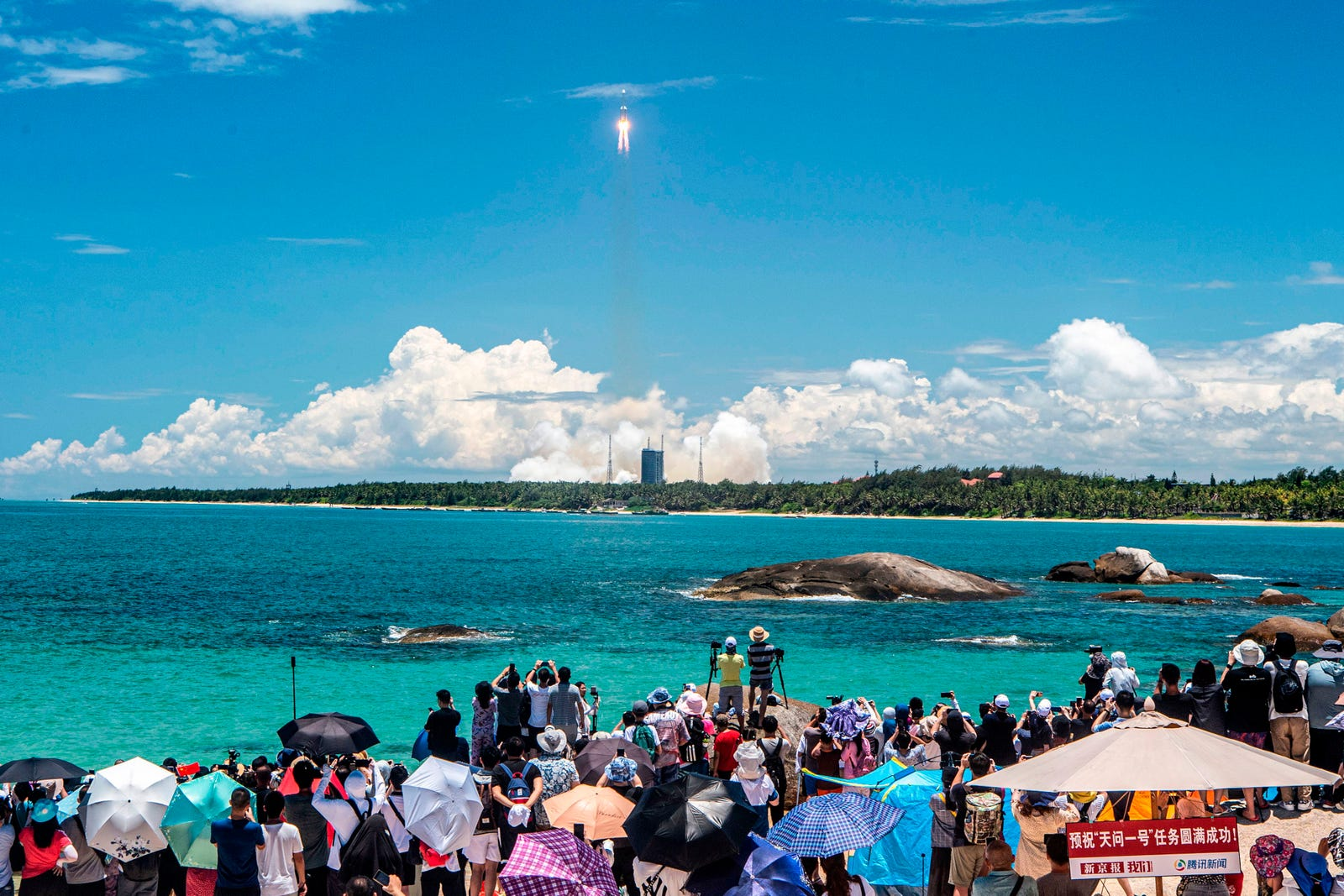 People watch a Long March-5 rocket, carrying an orbiter, lander and rover as part of the Tianwen-1 mission to Mars, lifting off from the Wenchang Space Launch Center in southern China's Hainan Province on July 23, 2020.
