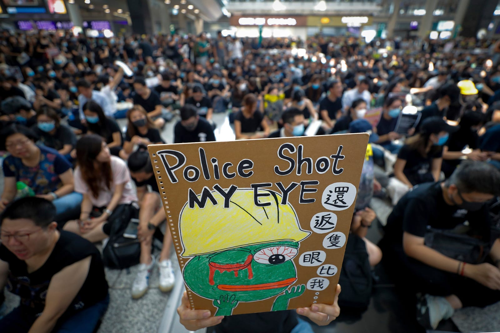 A protester displays a placard during a sit-in protest at the arrival hall of the Hong Kong International Airport in Hong Kong, Monday, Aug. 12, 2019.
