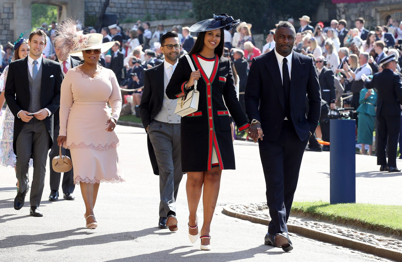 Idris Elba and Sabrina Dhowre followed by Oprah Winfrey (fourth right) arrive at St George's Chapel at Windsor Castle for the wedding of Meghan Markle and Prince Harry on May 19, 2018, in Windsor, England.