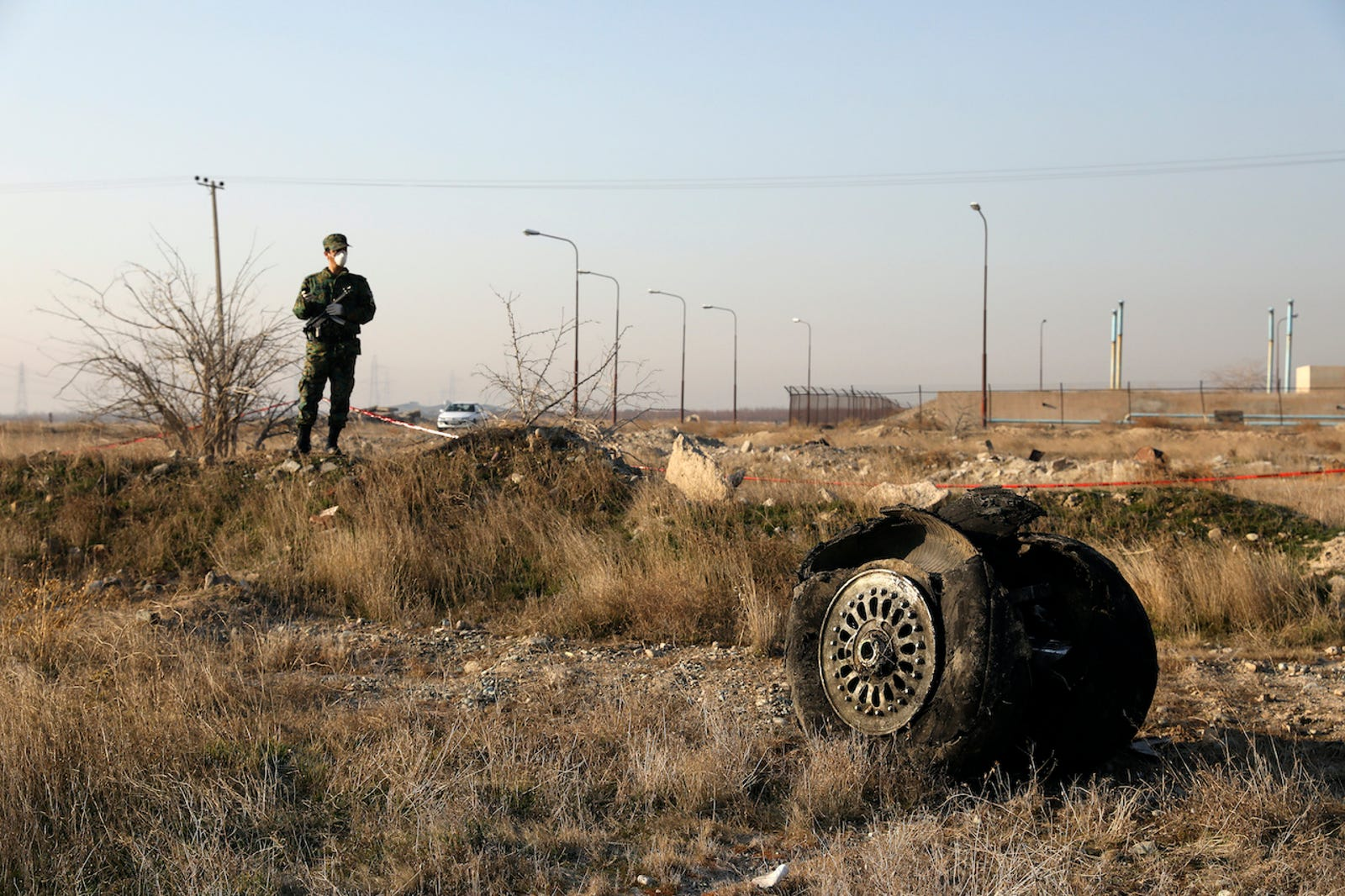A police officer stands guard as debris is seen from an Ukrainian plane which crashed in Shahedshahr, southwest of the capital Tehran, Iran, Wednesday, Jan. 8, 2020.