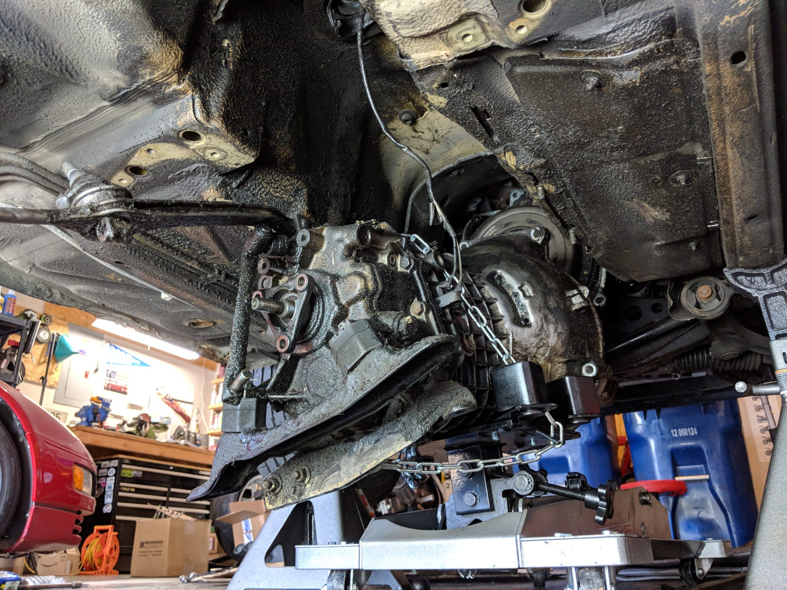 The transmission being lowered from the car.