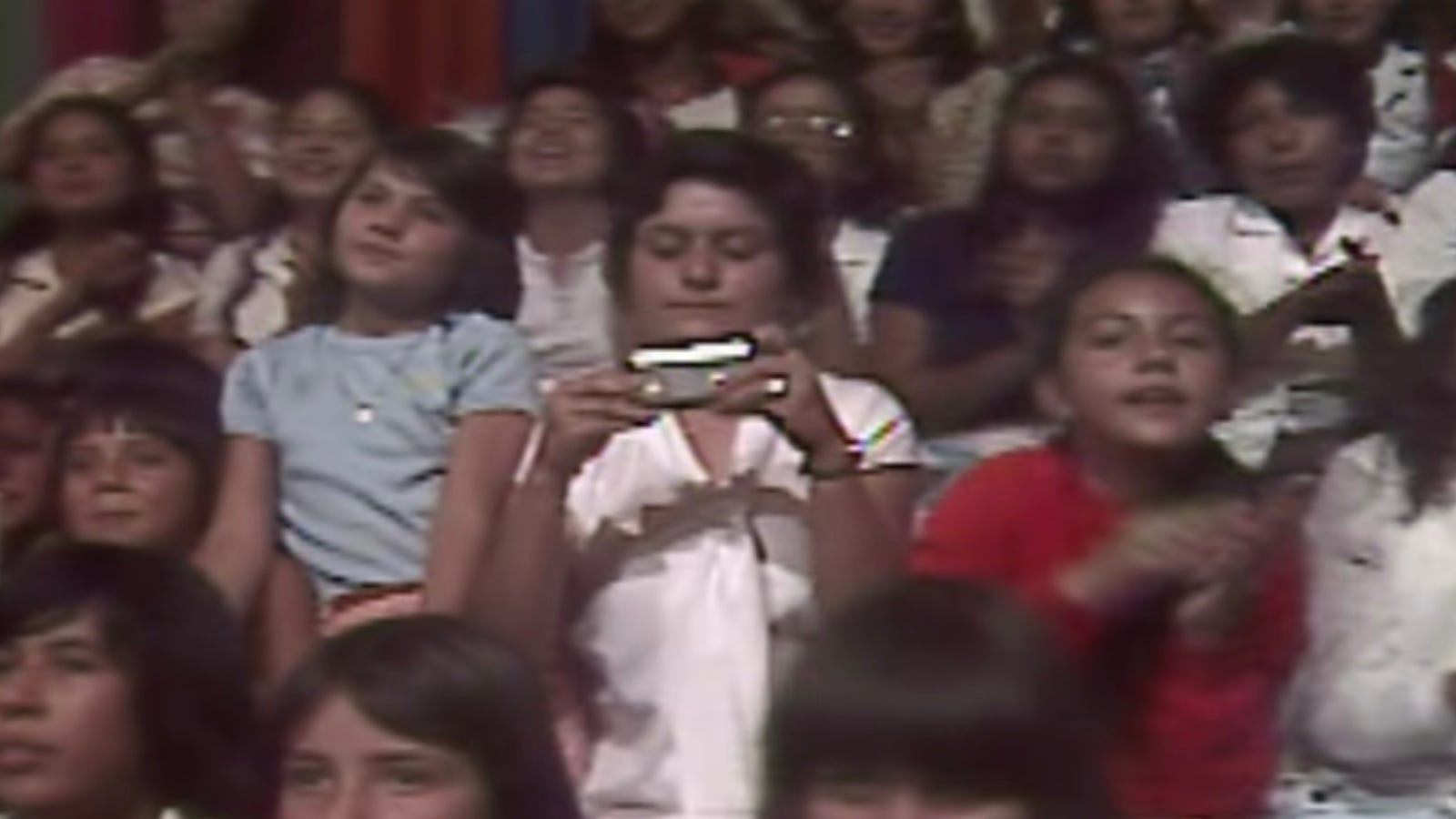 1/3: La mujer mira la supuesta pantalla del supuesto smartphone