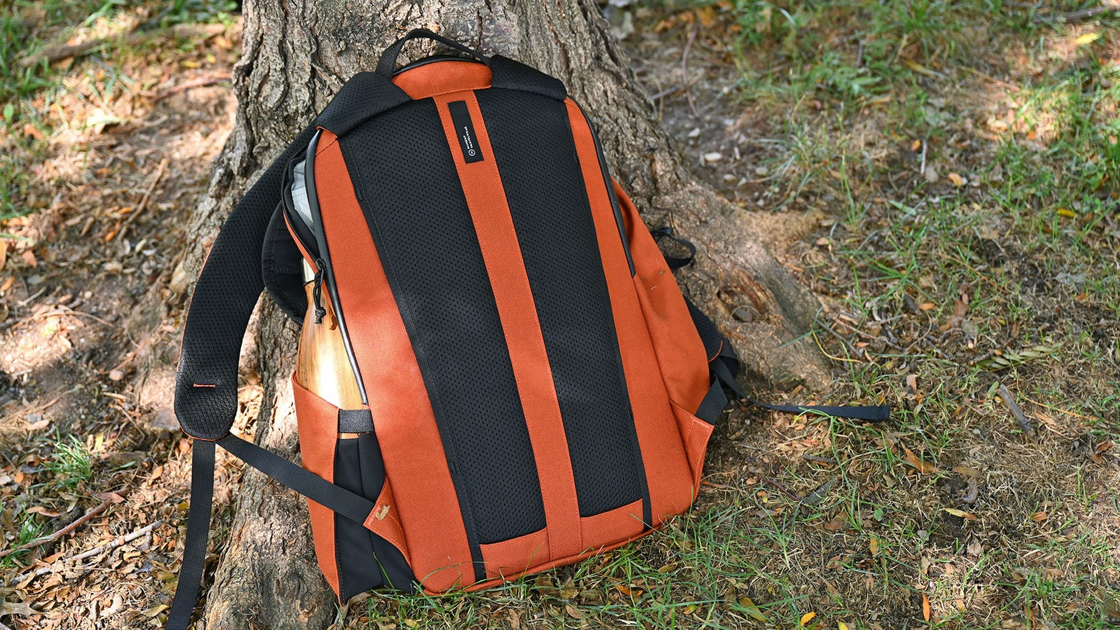 The back of the MTW Backpack features padded mesh for comfort and a pass-through slip for sliding over the handle of rolling luggage. Also, if orange isn't your thing, the backpack is available in olive and black too.