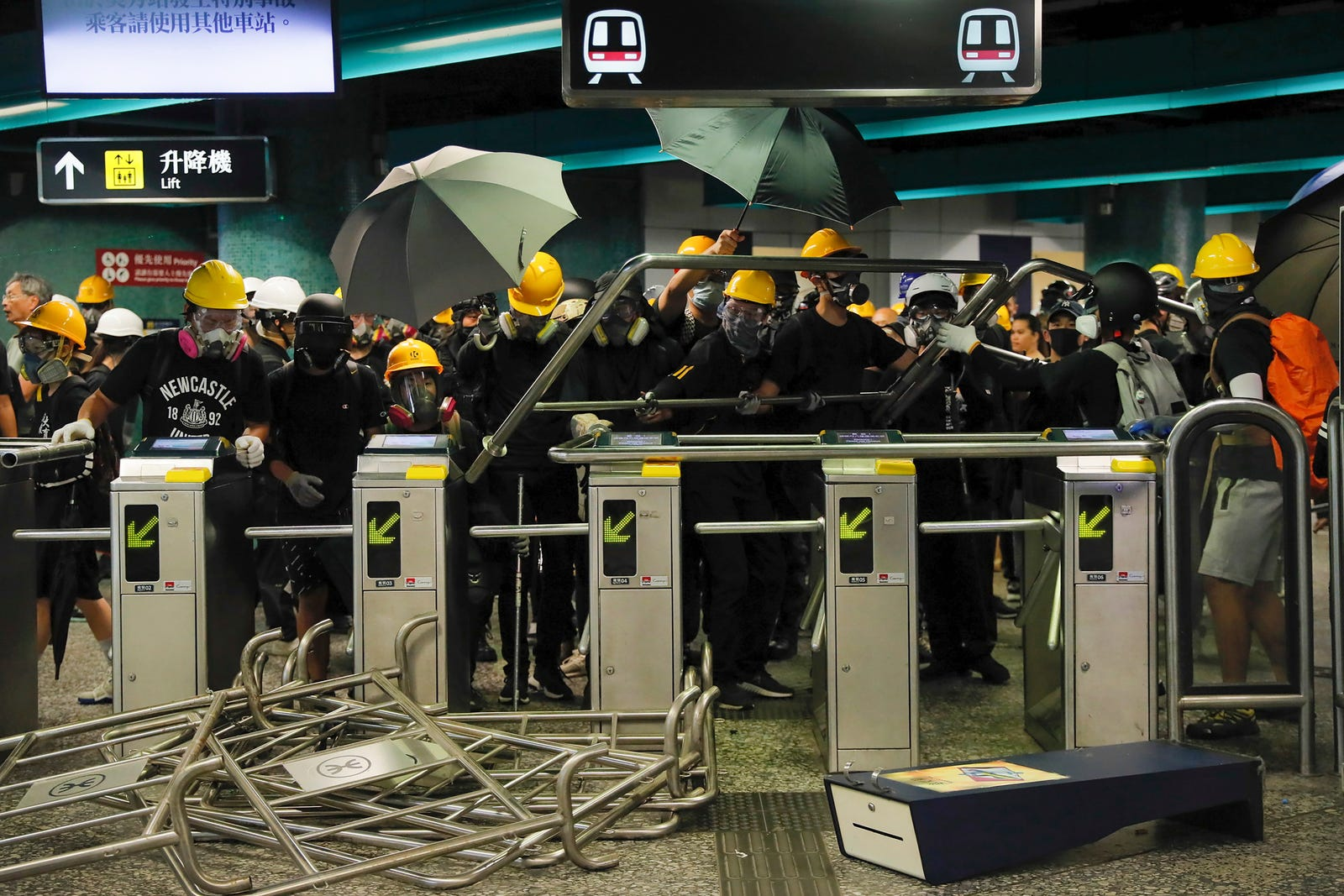 Protesters use steels barricades to form a defensive line inside the Quarry bay MTR station as they face with riot police in Hong Kong, Sunday, Aug. 11, 2019.