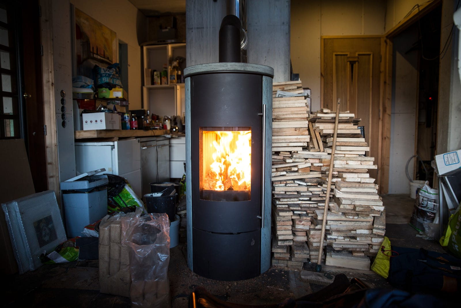 Frank's wood stove and the reclaimed wood he uses as fuel (Photo: Adam Clark Estes)