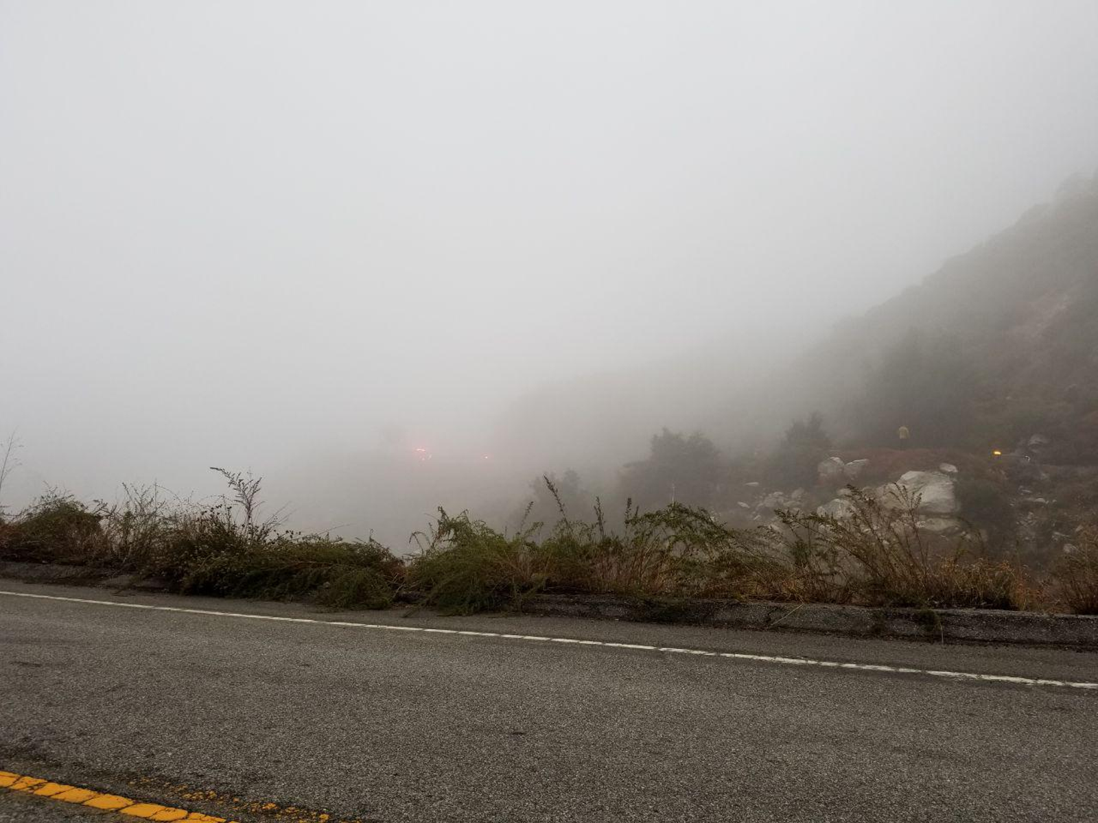 Flashing lights across the ravine on the other side of a corner. Lots of mist and rain on and off all day. The first rain will make the road greasy even on roads like this one that aren't traveled as much.