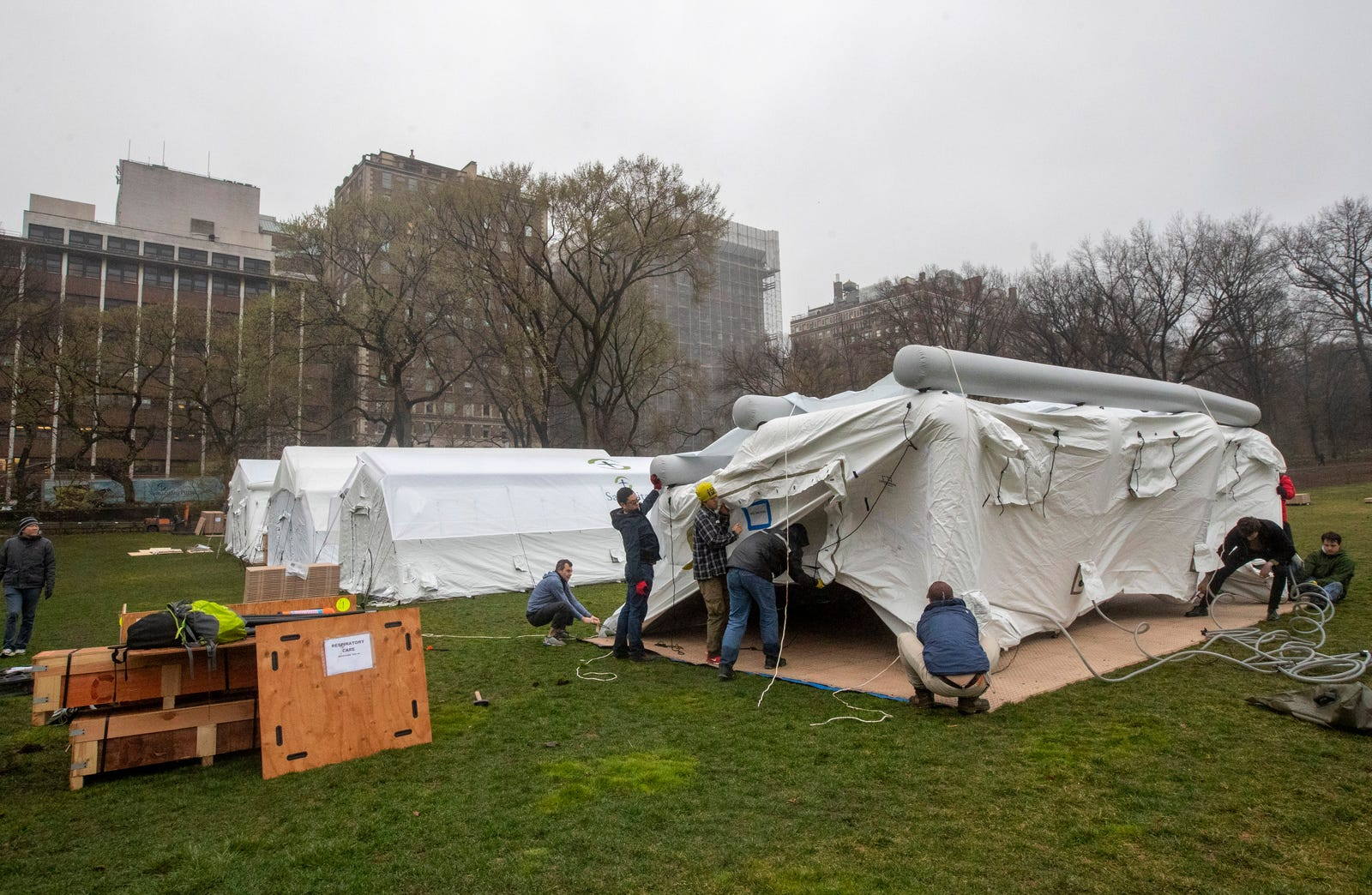 A Samaritan's Purse crew works on building an emergency field hospital equipped with a respiratory unit in New York's Central Park across from the Mount Sinai Hospital, Sunday, March 29, 2020.