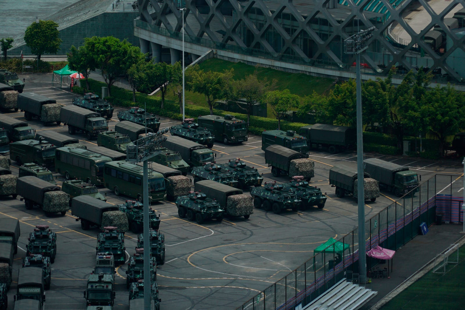 Armored vehicles and troop trucks are parked in a lot by Shenzhen Bay Stadium in Shenzhen, China Friday, Aug. 16, 2019. Armored vehicles belonging to China's paramilitary People's Armed Police were parked in the sports complex across the border in Hong Kong, in what some have interpreted as a threat against pro-democracy protesters.