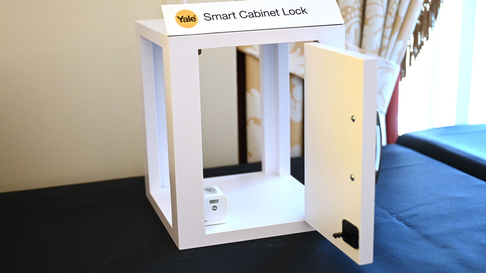 The $80 Smart Cabinet Lock is the small white box in the corner, which sits inside your cupboard and latches on to a plastic tab that you install on the cabinet's door.