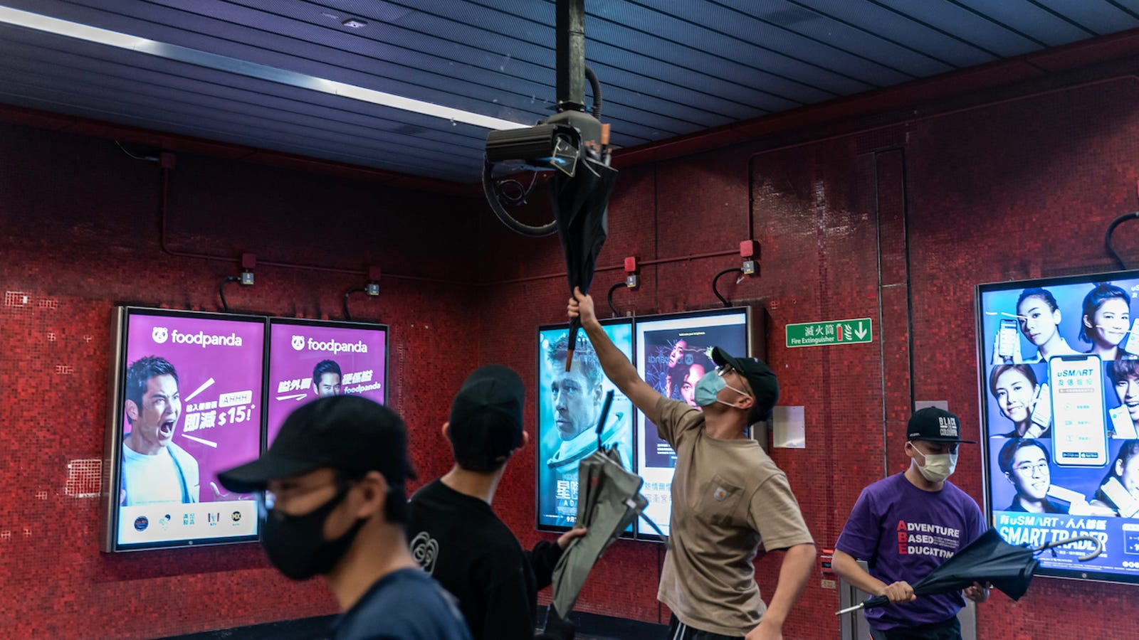 Pro-democracy protesters break a surveillance camera at a Tai Koo MTR station on October 3, 2019 in Hong Kong
