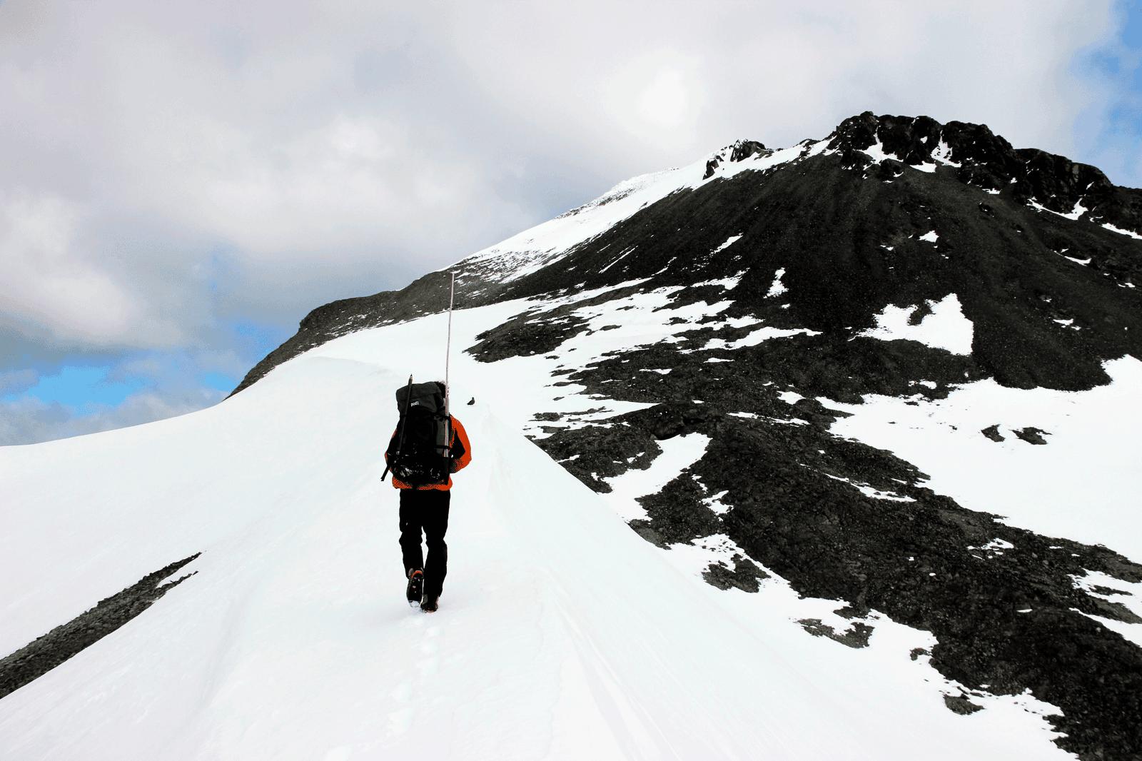 Stef Bokhorst exploring snow ridge toward mountain peak on Jenny Island