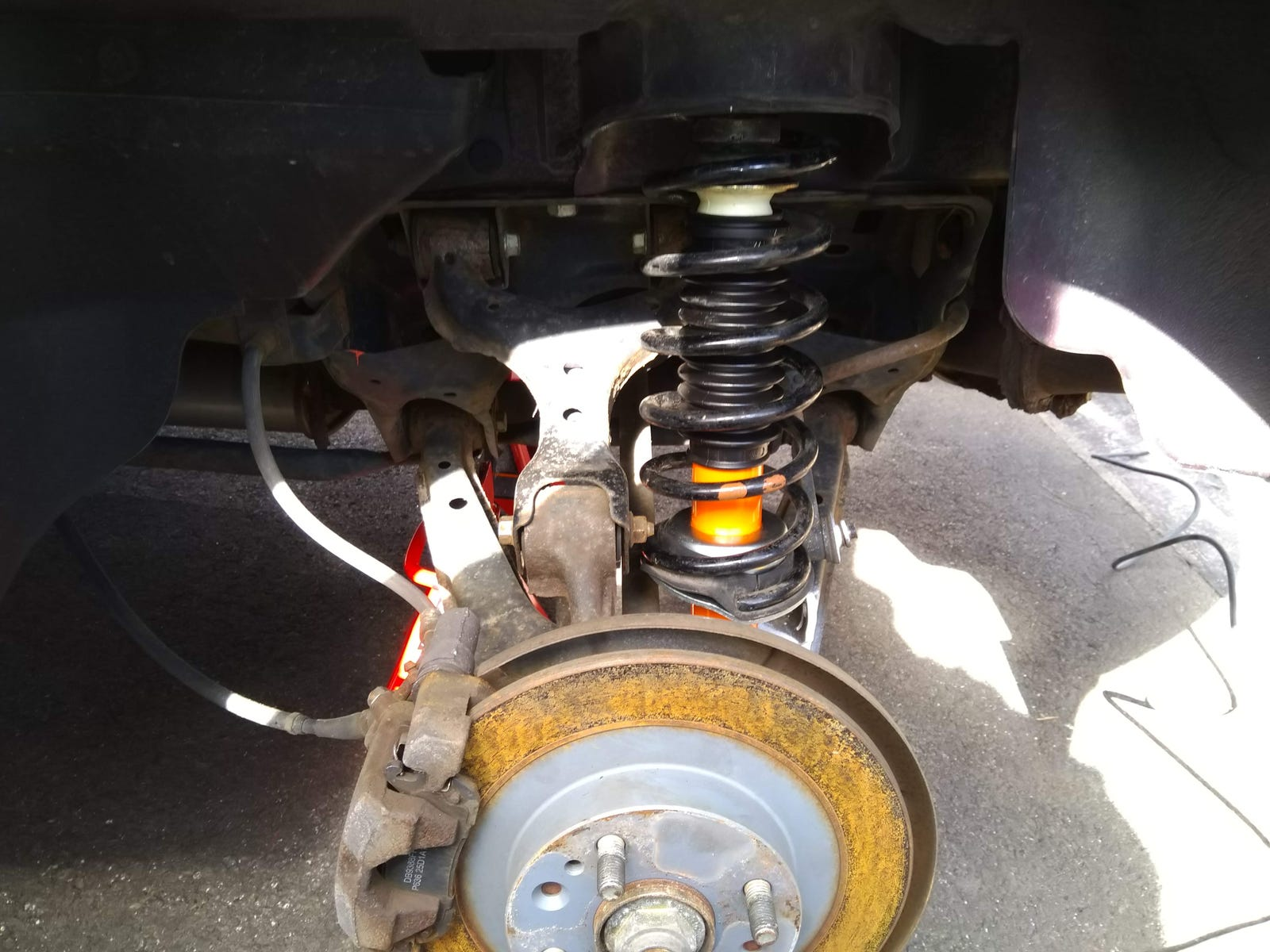 New shock absorber assembly in place and ready to be fastened to the top  hat. Note the brown dots on the spring, indicating that these are Sport  Package rear springs; standard rear springs have purple dots.