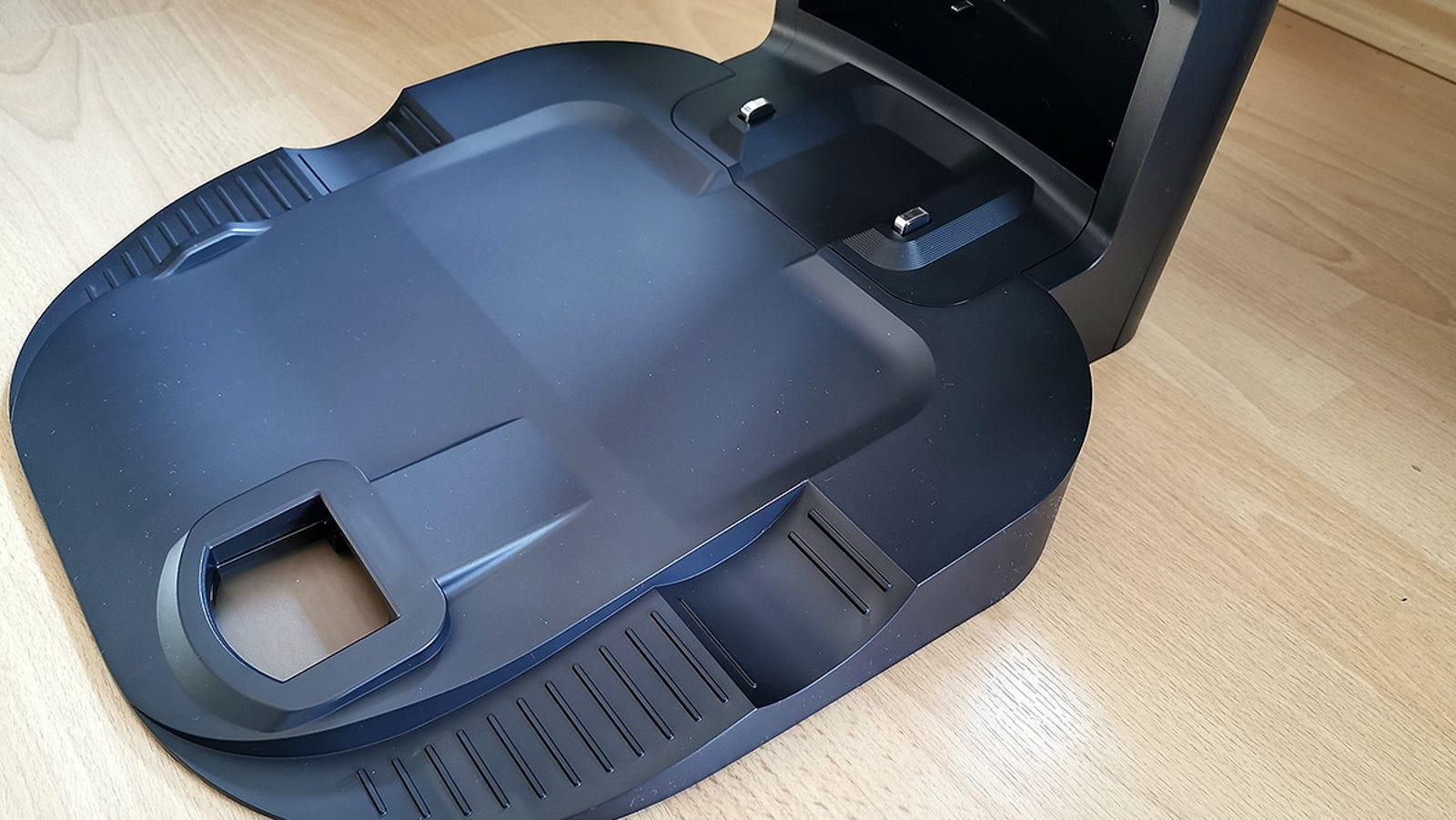 La parte inferior de la base de carga, con el agujero para el vaciado de depósito y los contactos de carga