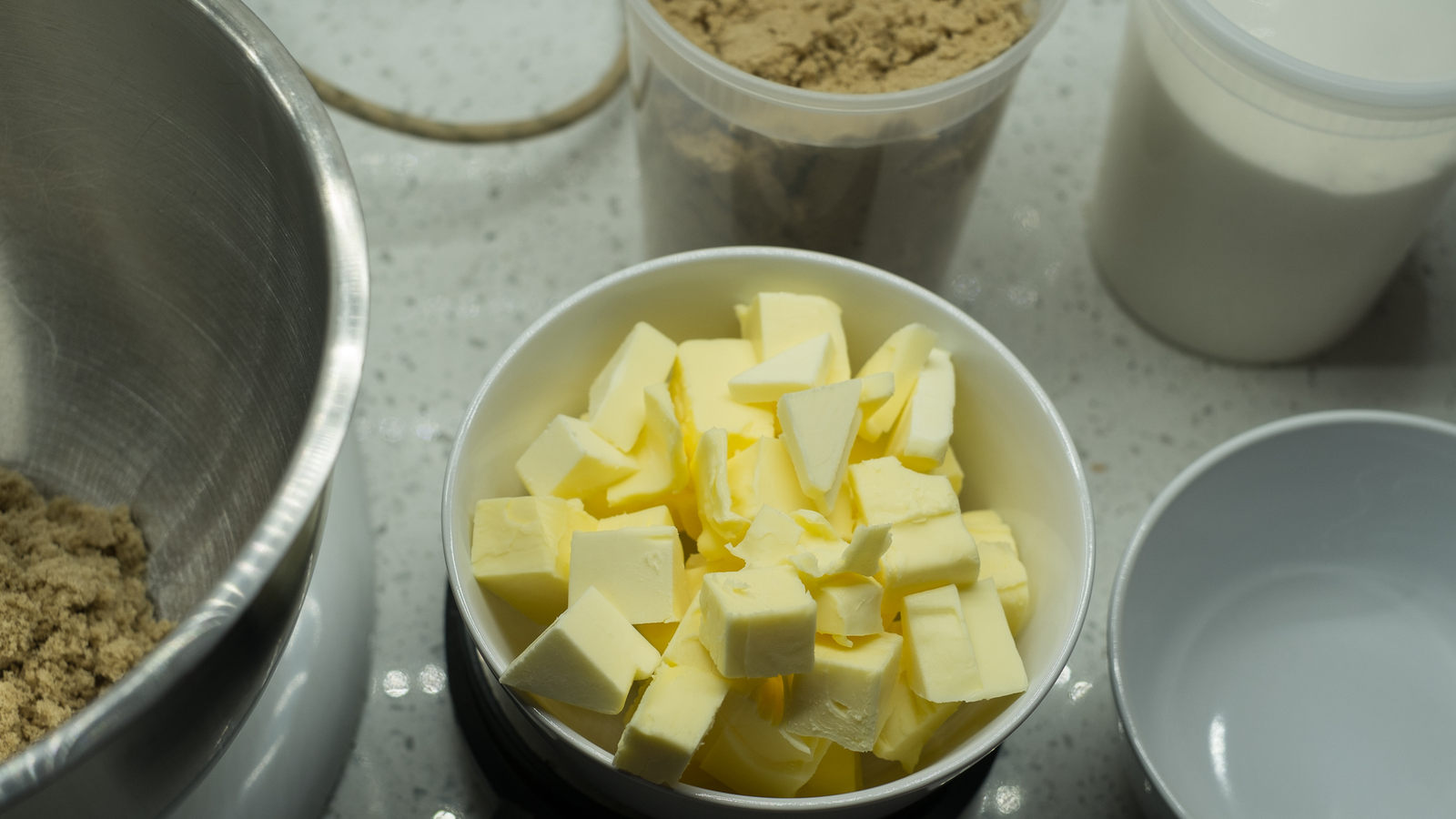 There's 255 grams of butter and 150 grams of sugar—100 white, 50 light brown—measured out here.