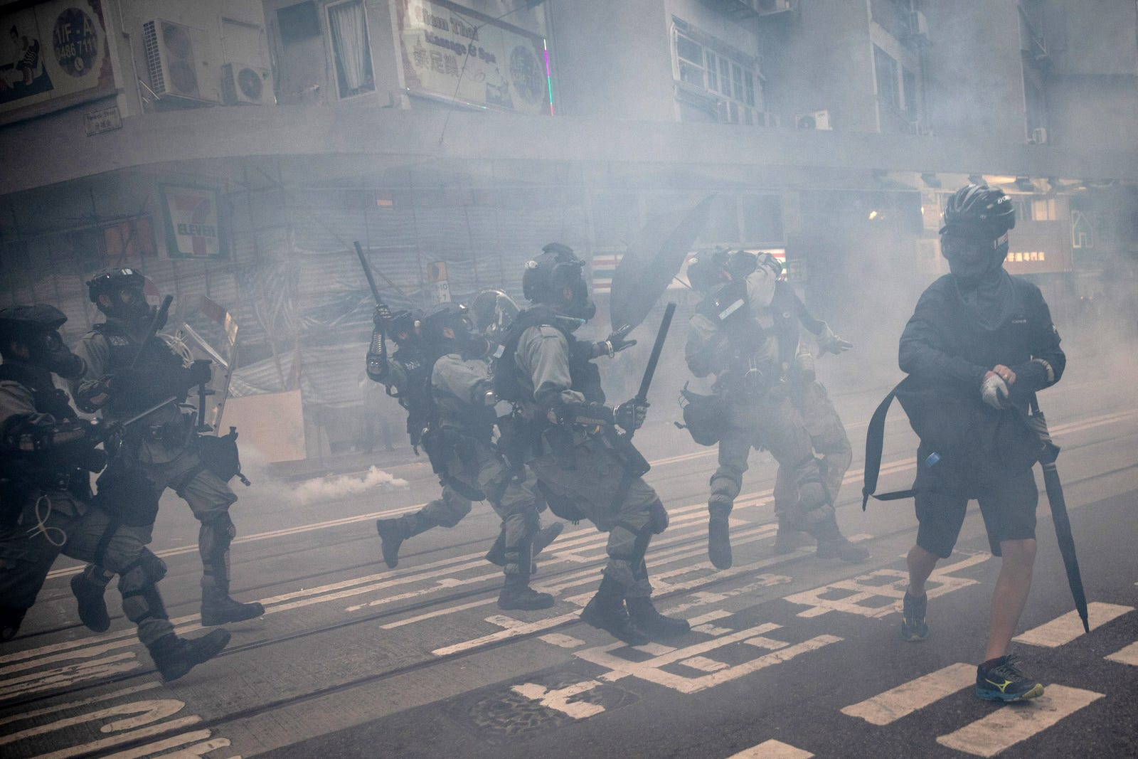 A pro-democracy protester runs from police as they arrest protesters during clashes in Wan Chai on October 01, 2019 in Hong Kong