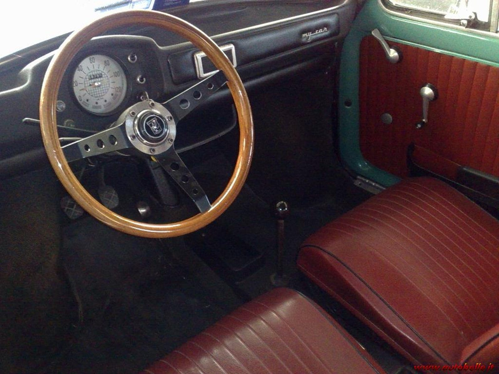 The very inviting wooden steering wheel of the 'My Car'. Note the redesigned and re-shaped padded dash and instrument cluster.