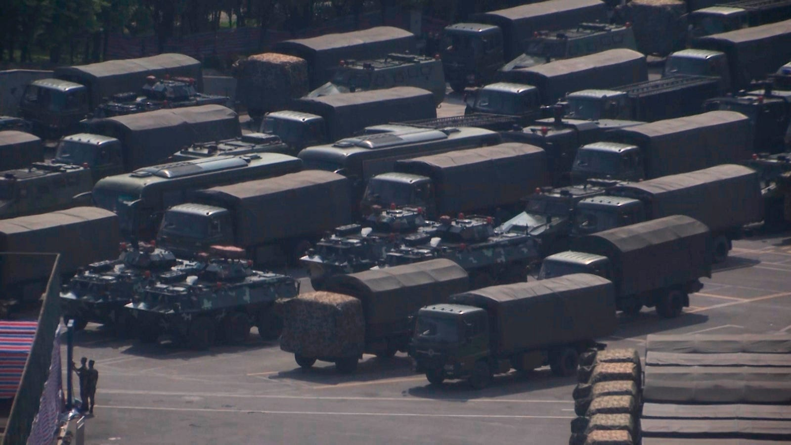In this image made from video, armed police vehicles are parked outside Shenzhen Bay Stadium in Shenzhen, near Hong Kong, Friday, Aug. 16, 2019. Satellite photos show what appear to be armored personnel carriers and other vehicles belonging to the China's paramilitary People's Armed Police parked in a sports complex in the city of Shenzhen, in what some have interpreted as a threat from Beijing to use increased force against pro-democracy protesters across the border in Hong Kong.