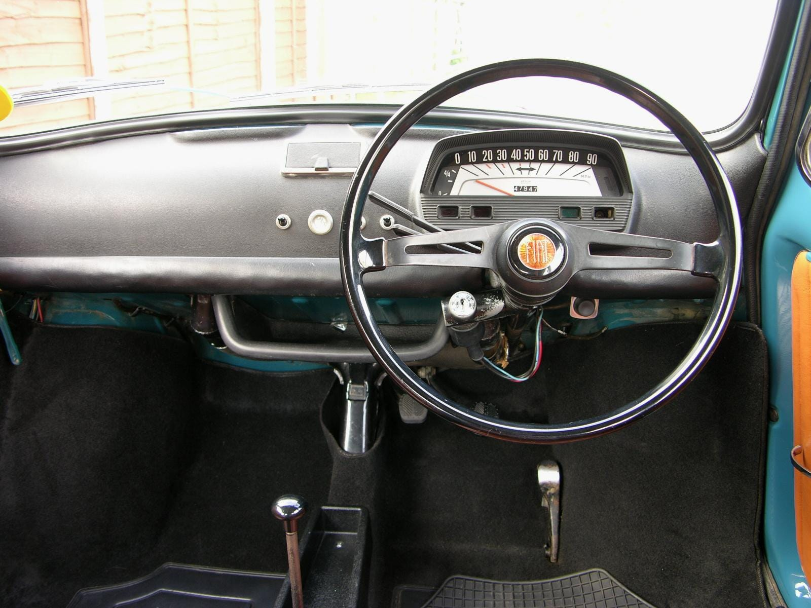 The matte anti-glare plastic dash cladding is clearly visible in the interior of this RHD-spec 500L. Note the blanking plug in the center of the dashboard to cover the hole the ignition switch previously took up on 500F, 500D and Nuova models. 500L cars also featured a new steering wheel - two metal central spokes flanking a FIAT badge with black plastic wheel.