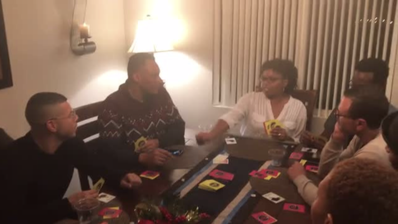 Friends shown playing the card game The Ultimate Clap Back.