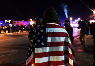 A protester wraps himself in a U.S. flag in Ferguson, Mo., Nov. 25, 2014, during demonstrations a day after violent protests and looting following the grand jury decision in the fatal shooting of 18-year-old black teenager Michael Brown.JEWEL SAMAD/AFP/Getty Images