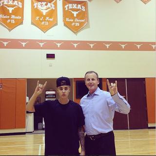 "Illustration for article titled Justin Bieber Does ""Hook 'Em Horns"" With Rick Barnes At Texas"