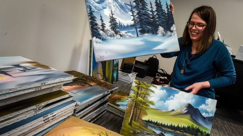 Sarah Stroll, executive assistant at Bob Ross, Inc., with a stack of Ross paintings on October, 15, 2018, in Herndon, Virginia.