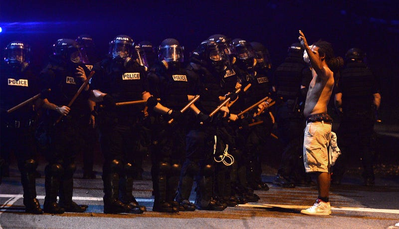A protester stands with arms raised near a line of officers from the Charlotte-Mecklenburg Police Department in riot gear Sept. 20, 2016, in Charlotte, N.C.Jeff Siner/Charlotte Observer/TNS via Getty Images
