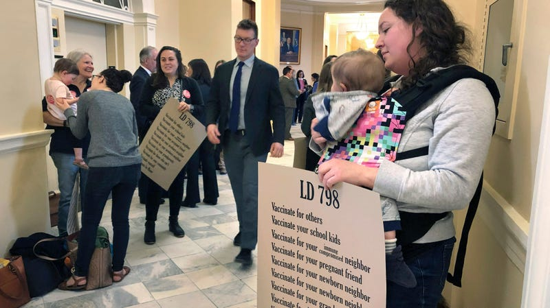 A woman holds her daughter with other mothers in a hallway, Thursday, May 2, 2019, at the Statehouse in Augusta, Maine, where the Senate was considering a bill ending non-medical vaccine exemptions. The bill passed and was signed by Governor Janet Mills (D) on Friday.