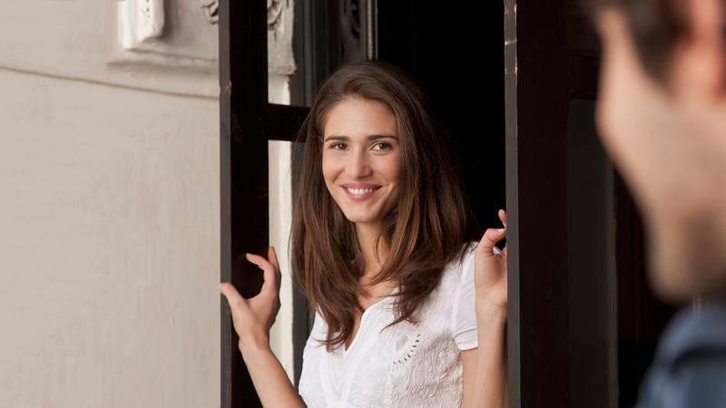 A woman standing near a door.