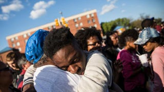 A man hugs a friend after being prayed over April 28, 2015, during a protest near the Baltimore CVS pharmacy that had been set on fire the day before during unrest after the funeral of Freddie Gray. Gray, 25, was arrested April 12, suffered a severe spinal cord injury while in police custody and died a week later.Andrew Burton/Getty Images