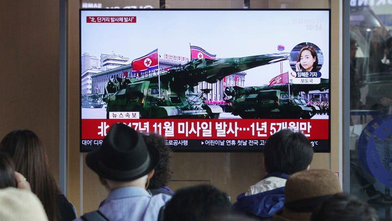 Commuters watch a news program on the TV at Seoul Railway Station in Seoul on May 4, 2019.