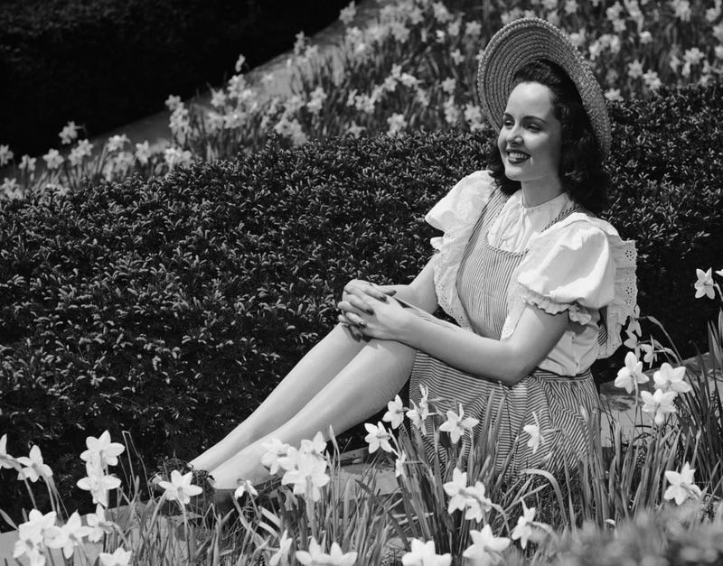 CIRCA 1950s: Portrait of woman surrounding by flowers. (Photo by George Marks/Retrofile/Getty Images)
