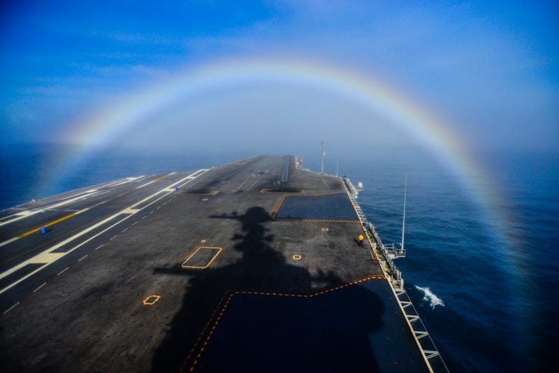 Illustration for article titled Check Out This Shot Of A US Navy Super Carrier Passing Through A Rainbow